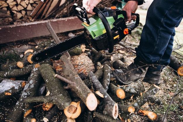 Een man snijdt brandhout met een zaag close-up