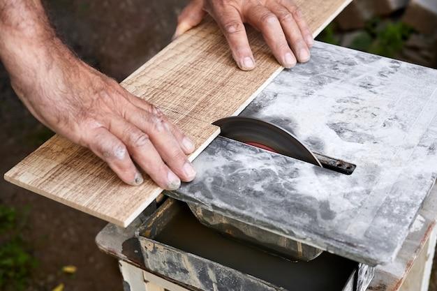 Een man snijdt een keramische tegel met behulp van een tegelsnijder met watergekoelde