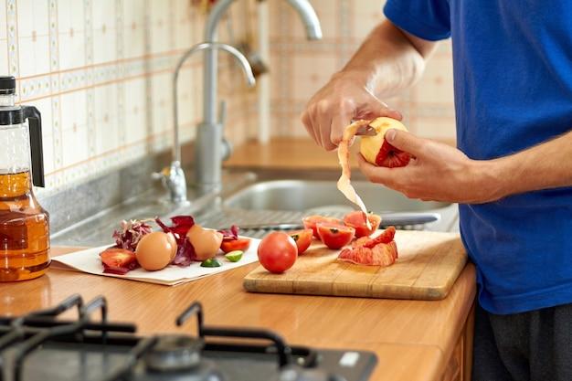 Een man snijdt met een mes een schil van een rode appel
