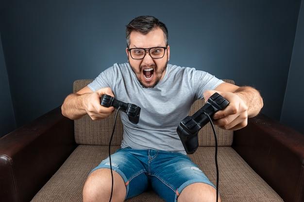 Een man speelt de console, videogames reageren sterk en emotioneel terwijl hij op de bank zit. vrije dag, entertainment, vrije tijd.