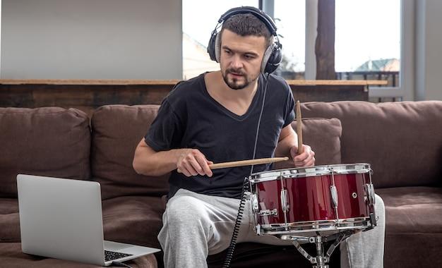 Een man speelt de trommel en kijkt naar het laptopscherm. het concept van online muzieklessen, lessen videoconferenties.