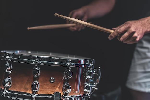 Een man speelt een snaredrum met stokken, een drummer speelt een percussie-instrument, close-up.