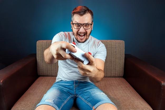 Een man speelt een videogameconsole terwijl hij op een bank zit. vrije dag, entertainment, vrije tijd.