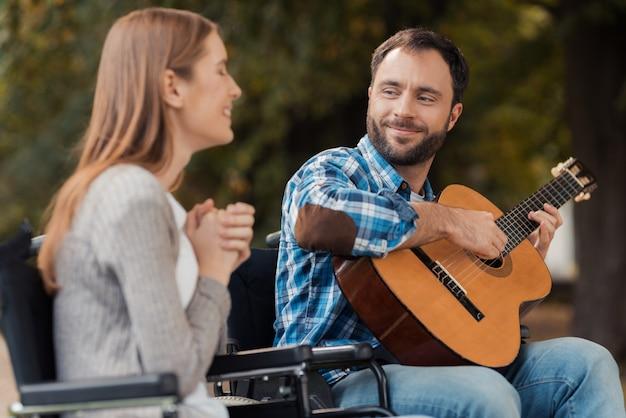 Een man speelt gitaar, de vrouw luistert en glimlacht.