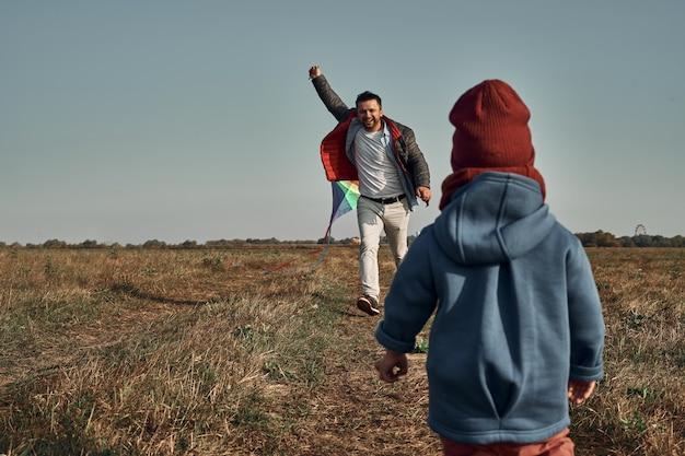 Een man speelt met een tweeling van twee jaar oud met een vlieger in een veld, een vuurtoren en gebouwen op de achtergrond. herfsttijd, buitenspellen.