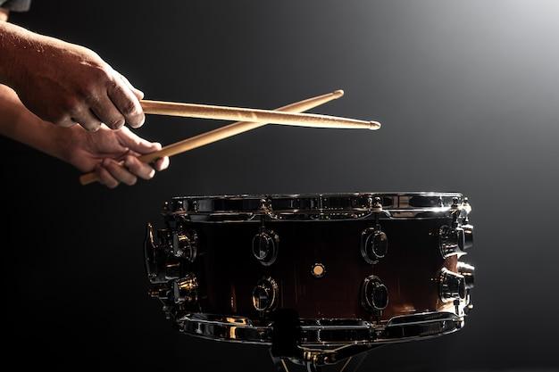 Een man speelt met stokken op een trommel, een drummer speelt een percussie-instrument, kopieer ruimte.