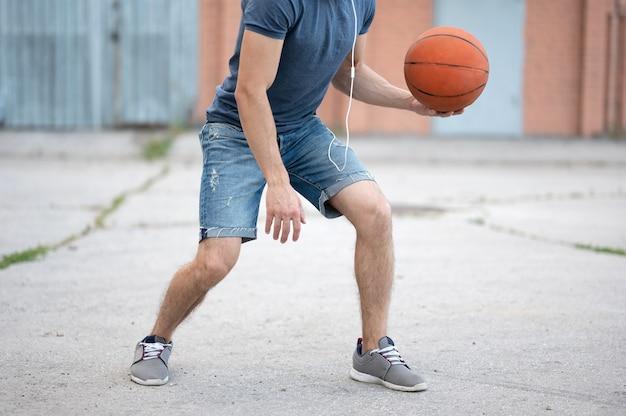Een man speelt overdag basketbal in de straat