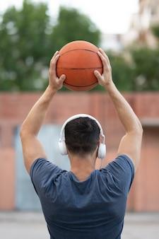 Een man speelt overdag basketbal op het erf van de straat