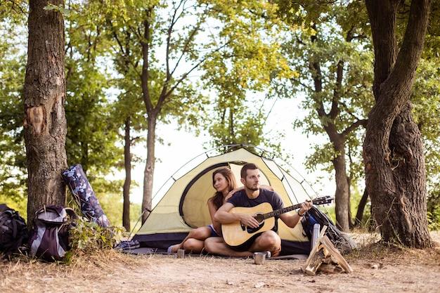 Een man speelt voor een vrouw op een gitaar in de buurt van een tent bij zonsondergang. huwelijksreis tijdens de wandeling