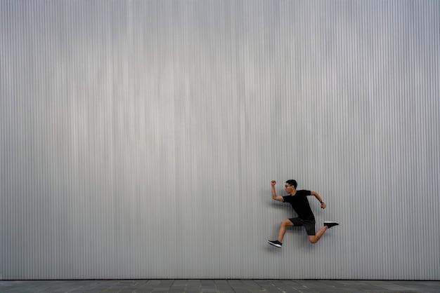 Een man springt in de lucht op een grijze gestructureerde achtergrond