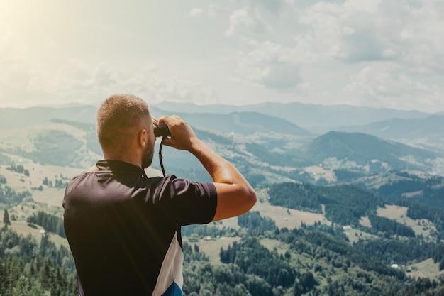 Een man staande op een boomstronk in de zomerbergen bij zonsondergang en genietend van het uitzicht op de natuur