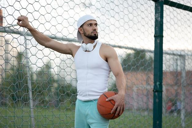 Een man staat bij een hek op straat met een basketbal in zijn hand