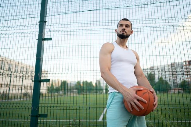 Een man staat bij een hek op straat, met een basketbal in zijn hand Premium Foto