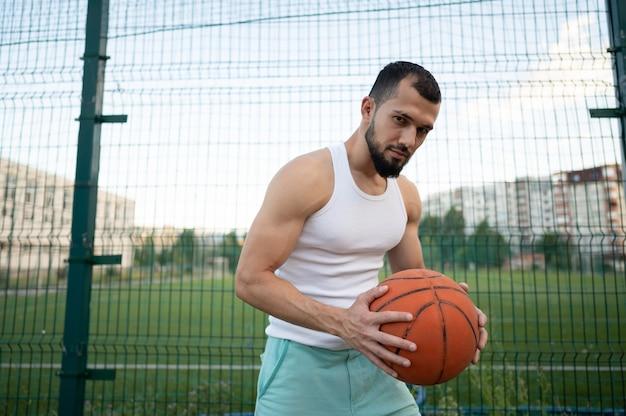 Een man staat bij een hek op straat, met een basketbal in zijn hand