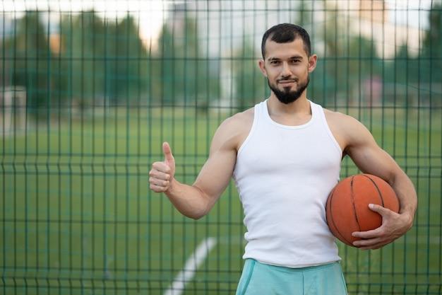 Een man staat bij het hek op straat, houdt een basketbal in zijn hand en laat zijn koelte zien