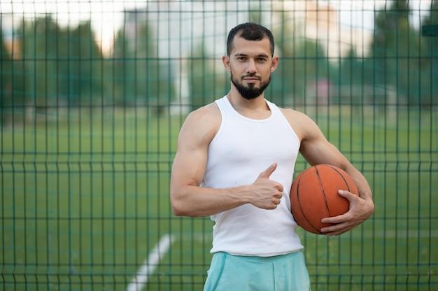 Een man staat bij het hek op straat, houdt een basketbal in zijn hand en toont zich cool