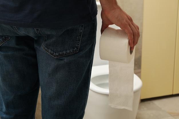 Een man staat bij het toilet en houdt toiletpapier vast