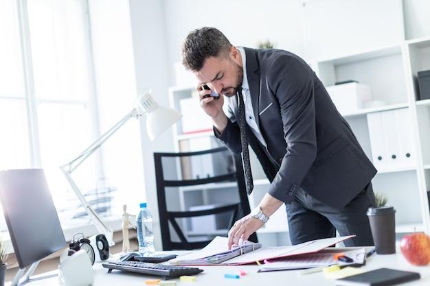 Een man staat in de buurt van een tafel op kantoor, telefoneert en bladert door documenten.