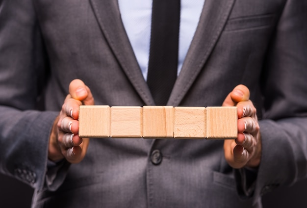 Een man staat in een pak en houdt kubussen vast.