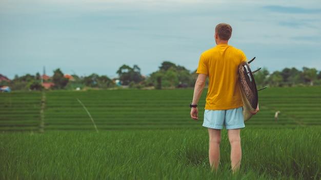 Een man staat in een rijstveld.
