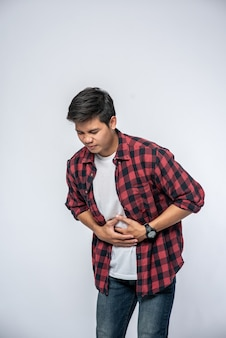 Een man staat met buikpijn en legt zijn hand op zijn buik.