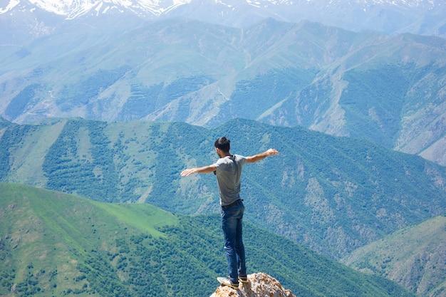 Een man staat met open armen op de top van een berg