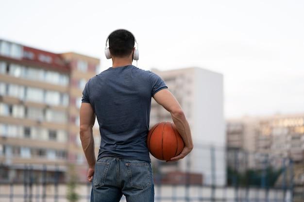 Een man staat met zijn achterkant van de stad en heeft een basketbal in zijn handen