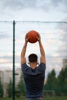 Een man staat met zijn rug tegen de achtergrond van een sportveld en houdt een basketbal in zijn handen
