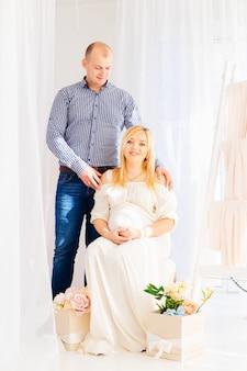 Een man staat naast zijn zwangere vrouw die op de stoel zit