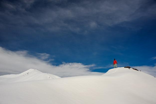 Een man staat op de met sneeuw bedekte berg, tegen de lucht