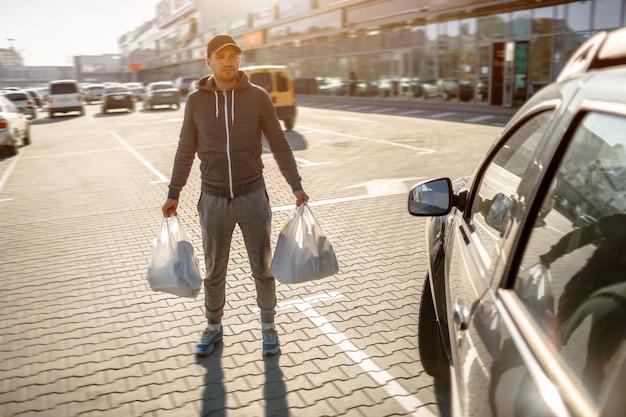 Een man staat op de parkeerplaats bij een winkelcentrum of een winkelcentrum.