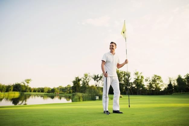 Een man staat op een golfbaan, heeft een golfclub en een vlag