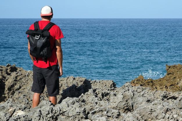 Een man staat op een lavarots, een oceaanstrand. achteraanzicht