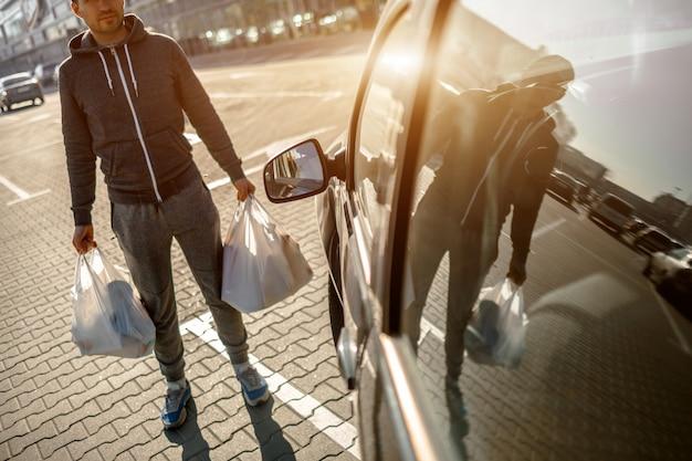 Een man staat op een parkeerplaats in de buurt van een winkelcentrum of een winkelcentrum. hij heeft alles met succes bij de supermarkt gekocht. plastic zakken gevuld met boodschappen, groenten en fruit, zuivelproducten.