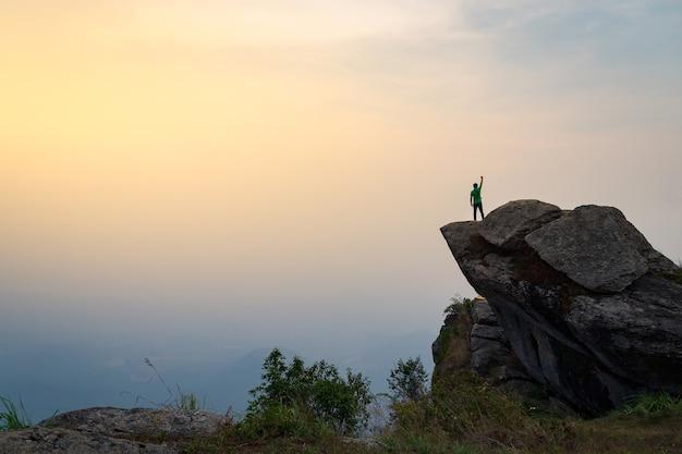 Een man staat op een steile klif met de achtergrond van de ochtendhemel.