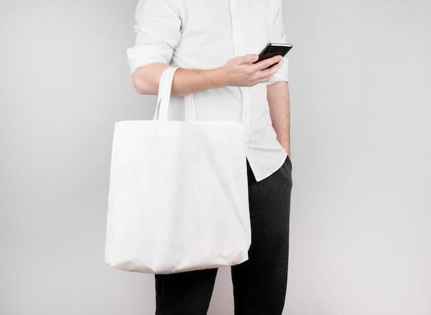 Een man staat op een witte muur, leest het nieuws aan de telefoon en houdt een ecologische tas van vlas op zijn elleboog. ecologie concept