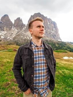 Een man staat tegen de achtergrond van de dolomieten in italië