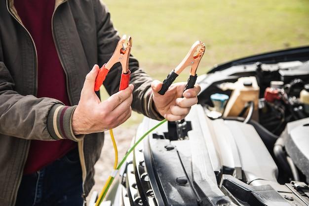 Een man staat voor een auto met een batterijjumper vast