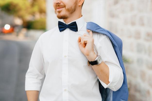Een man staat voor een wit bakstenen huis in het oude centrum van perast en houdt een jas over zijn schouder
