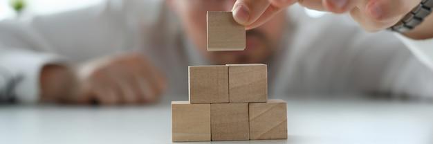 Een man stapelt houten blokken op een tafel close-up