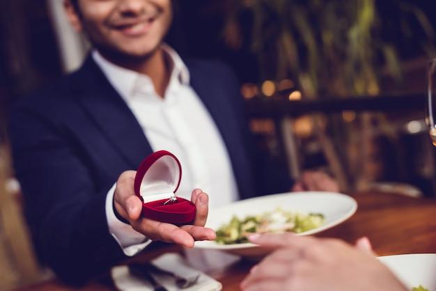 Een man stelt een vrouw voor en geeft haar een ring.
