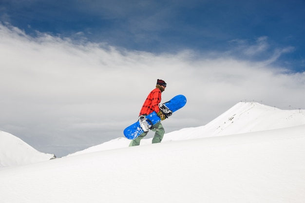 Een man stijgt op naar de met sneeuw bedekte berg en houdt een blauw snowboard tegen de lucht
