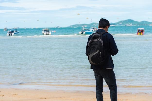 Een man stond te wachten op een boottocht op het strand.
