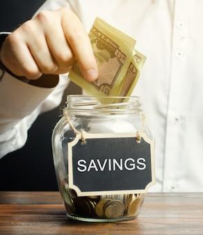 Een man stopt dollars in een glazen pot besparingen.