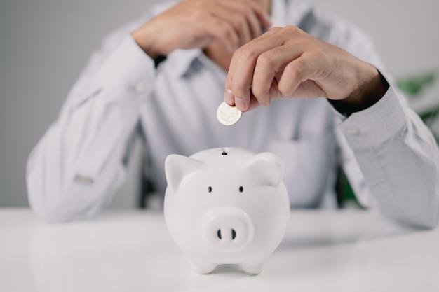 Een man stopt een munt in een spaarvarken. nadenken over wat te doen met het geld.