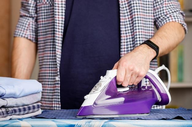 Een man strijkt een overhemd op een strijkplank met een strijkijzer. dagelijkse huishoudelijke taken.