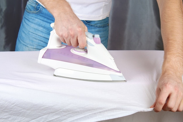 Een man strijkt linnen met een strijkijzer op een strijkplank.