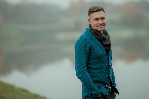 Een man succesvol en knap in een groene trui op de achtergrond van het meer