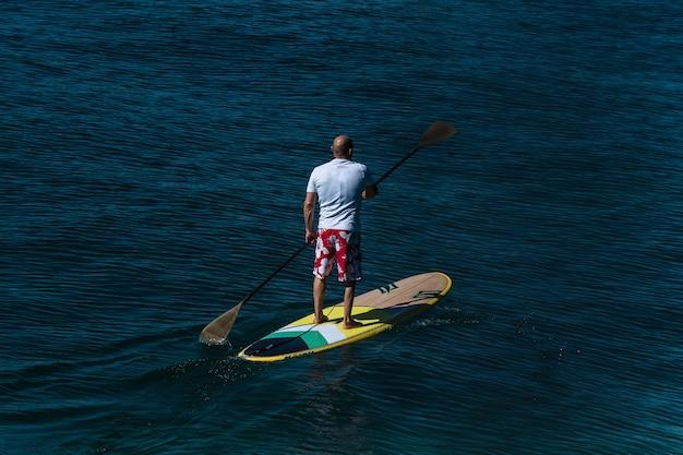 Een man surft met een peddel op de zee. sup