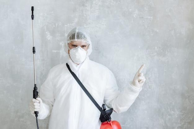 Een man tegen een betonnen muur in een pak met een desinfecterende spray om huishoudelijke artikelen en meubels te desinfecteren. het concept van een pandemische desinfectie van coronavirus of covid-19. huis desinfectie